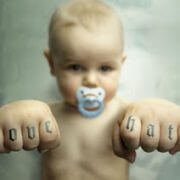 baby with knuckle tattoo